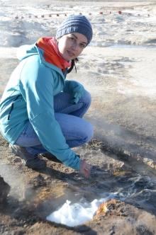 Julie accroupie devant un geyser d'eau chaude